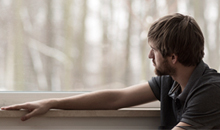 unidentified man with beard looking pensively out a window